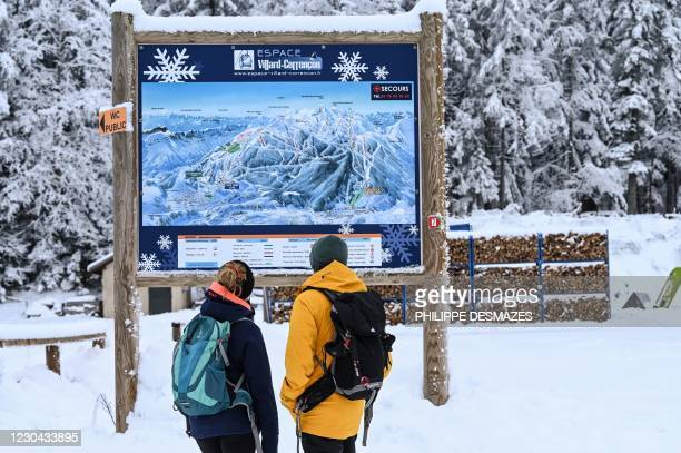 Two people watch the slopes' map on January 5, 2021 in Villard-de-Lans ski resort near Grenoble in the Vercors range, as French government's decision...