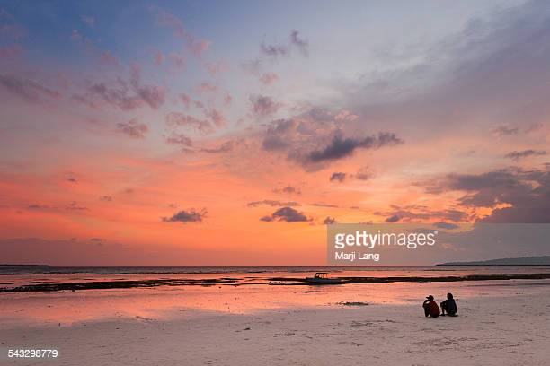 Two people watching sunset on the beach