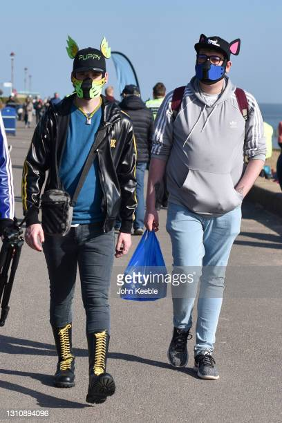 Two people wearing dog and cat style face masks with ears walk along the promenade on a warm sunny Easter Sunday at Chalkwell beach on April 04, 2021...