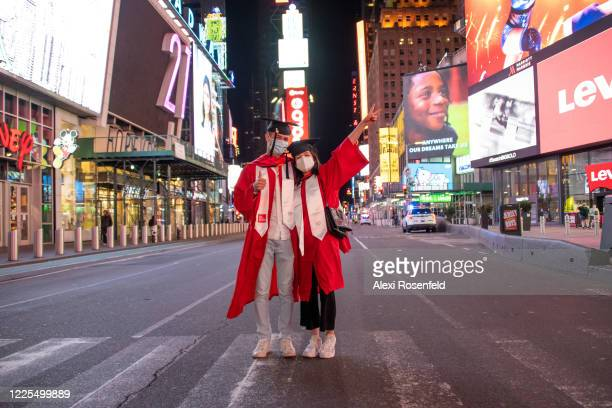 Two people wearing masks, graduation caps and gowns pose in the middle of an empty 7th Avenue in Times Square amid the coronavirus pandemic on May...