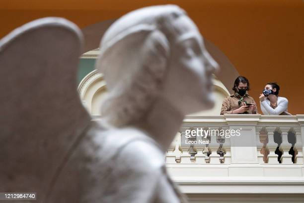 Two people wearing masks look from a balcony as the cast of an angel by Matteo Civitali is seen in the V&A Museum on March 17, 2020 in London,...