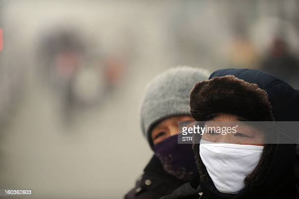 Two people wearing masks ride a bike in the heavy smog on a street of Haozhou central China's Anhui province on January 30 2013 Across China public...