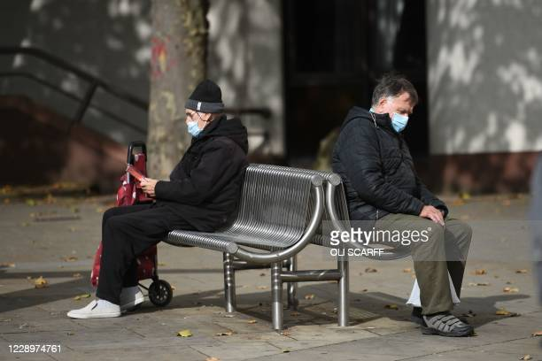 Two people wearing protective face masks to restrict the spread of coronavirus covid-19 rest on seats in central Nottingham in central England on...
