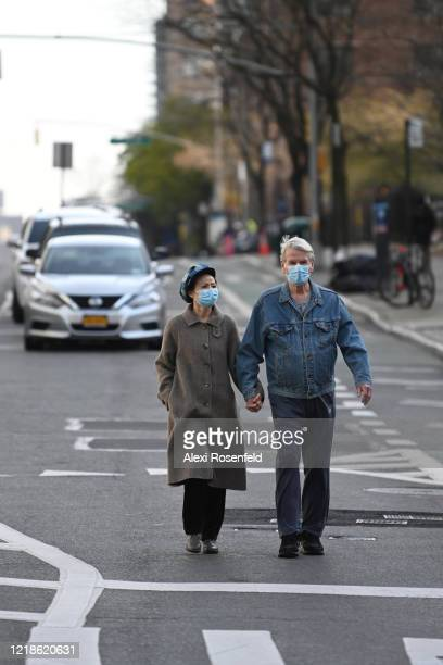 Two people wearing protective masks hold hands while walking down 1st Avenue amid the coronavirus pandemic on April 12 2020 in New York City United...