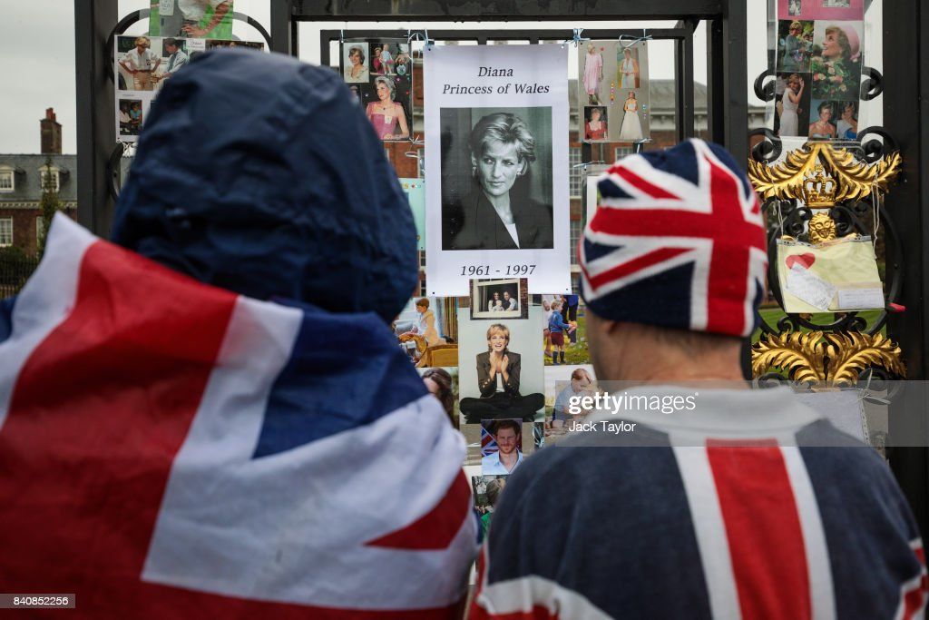 Two people wearing Union Jack outfits pause in front of floral tributes, photographs and messages on an entrance gate to Kensington Palace ahead of the 20th anniversary of the death of Diana, Princess of Wales on August 30, 2017 in London, England. On August 31, 1997 Princess Diana was fatally injured, aged 36, in a high speed car crash in a Paris, France. The months following her death saw a huge public outpouring of grief with a sea of tributes left by members of the public outside Kensington Palace.