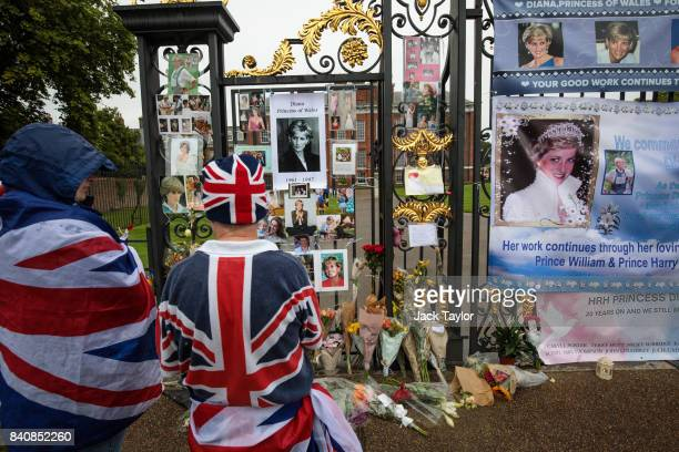 Two people wearing Union Jack outfits pause in front of photographs and messages on an entrance gate to Kensington Palace ahead of the 20th...