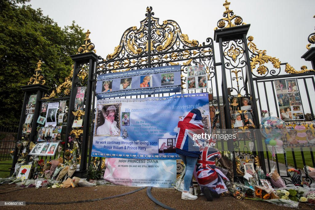 Two people wearing Union Jack outfits secure a banner among floral tributes and messages on an entrance gate to Kensington Palace ahead of the 20th anniversary of the death of Diana, Princess of Wales on August 30, 2017 in London, England. On August 31, 1997 Princess Diana was fatally injured, aged 36, in a high speed car crash in a Paris, France. The months following her death saw a huge public outpouring of grief with a sea of tributes left by members of the public outside Kensington Palace.