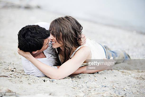 Two people who love each other laying in sand