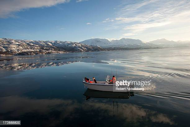 Two people with a dog travel by motorboat through the bay to fish March 4 2013 in Narvik Norway During 1940 Narvik was invaded by the German navy and...