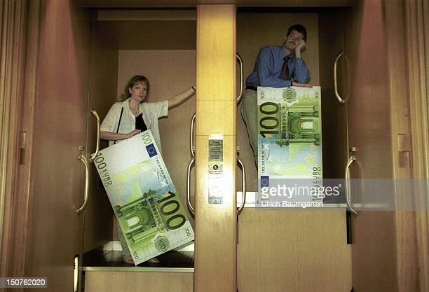Two people with big 100 Euro notes in a paternoster