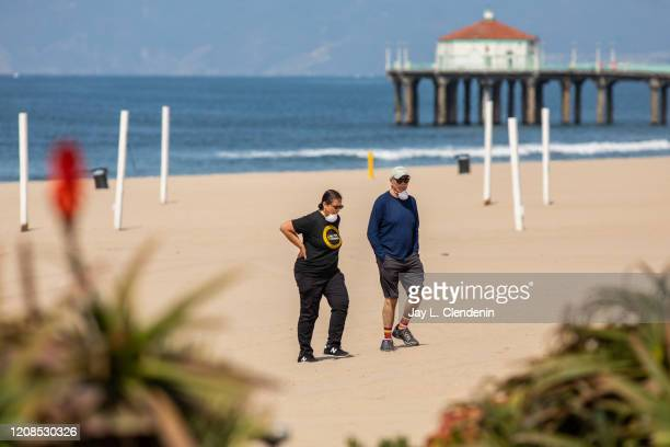 Two people with face masks walk on the beach of Manhattan Beach, CA, even as all beaches of Los Angeles county, are closed in an effort to slow the...
