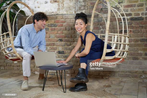 two people with laptop on swing chairs - employee stock pictures, royalty-free photos & images