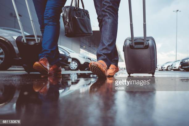 two people with luggage walking at parking lot - car park stock pictures, royalty-free photos & images