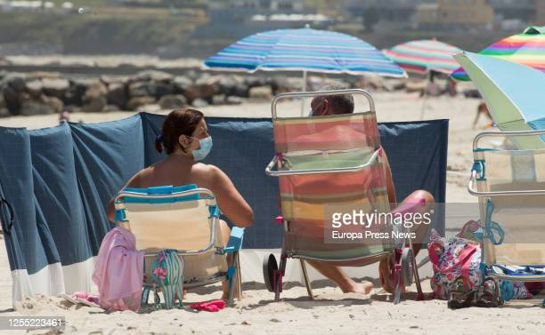 Two people with masks sunbathe on the beach of A Rapadoira in Foz in the region of A Mariña Lugo on July 09 2020 in Foz Spain On July 5 the Xunta...