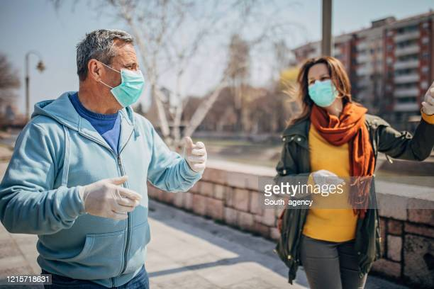 two people with protective mask walking on the street in safe distance - social distancing stock pictures, royalty-free photos & images