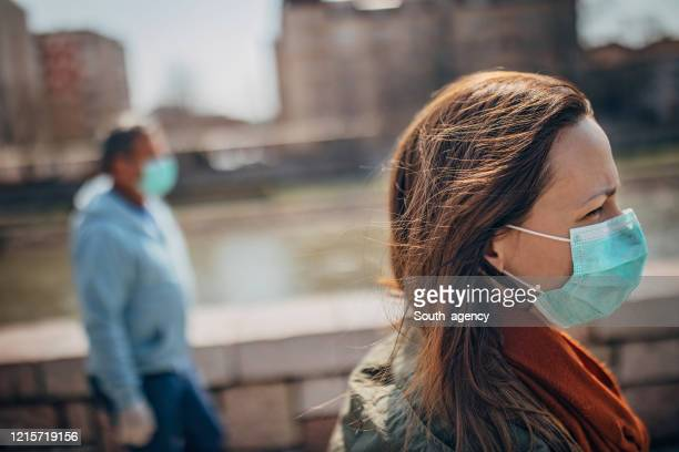 two people with protective mask walking on the street in safe distance - avoidance stock pictures, royalty-free photos & images
