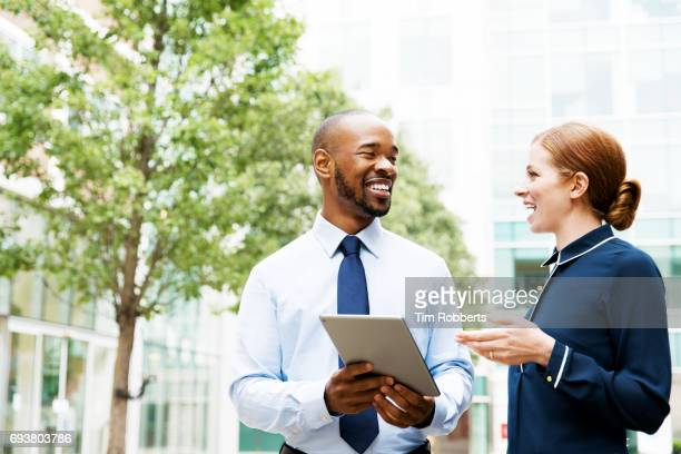 two people with tablet in financial district - business meeting stock pictures, royalty-free photos & images