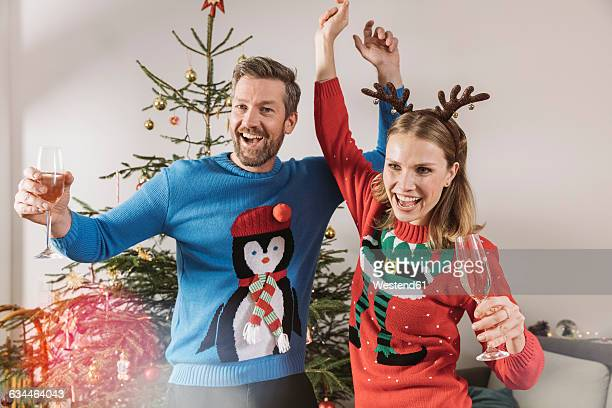 Two people with ugly Christmas sweaters dancing in front of tree