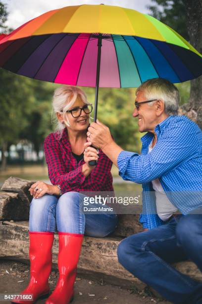 Two people with umbrella in autumn rainy day