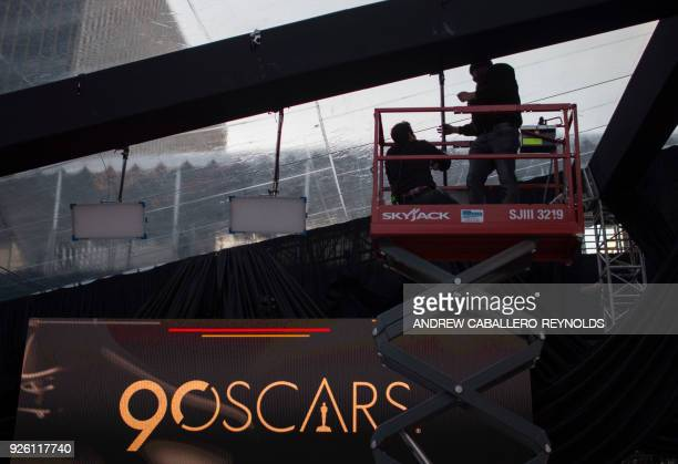 Two people work on the roof over the red carpet during preparations for the 90th annual Academy Awards week in Hollywood California on March 1 2018 /...