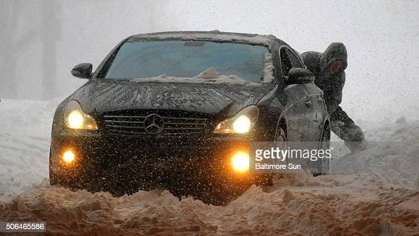Two people work together trying to extract their a Mercedes Benz rearwheel drive car that kept spinning wheels on US Route 40 in Baltimore on...