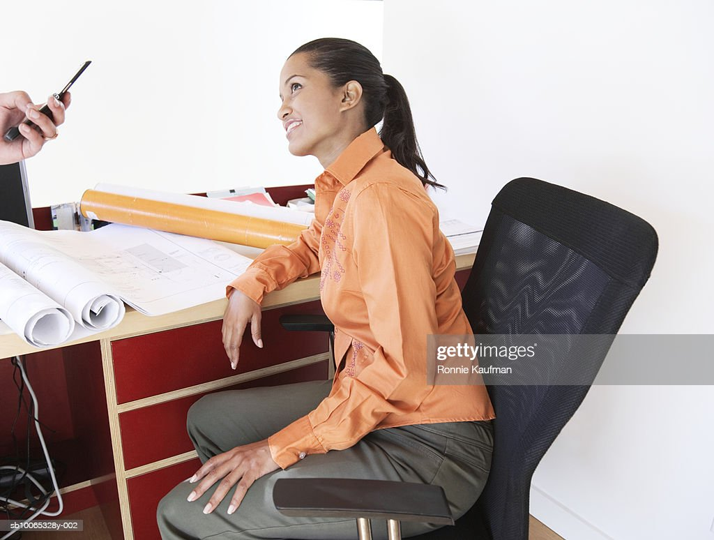 Two people working at home, one using mobile phone : Foto stock
