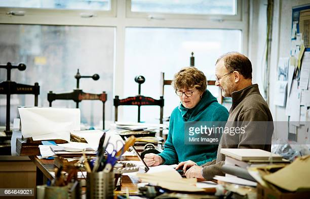 Two people working in a book binding business. Surrounded by tools and book presses.
