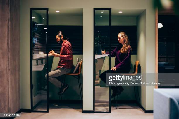 two people working in a workplace in separate cells keeping apart, social distancing - new normal concept stock pictures, royalty-free photos & images