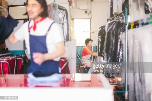 Two people working in dry cleaning shop