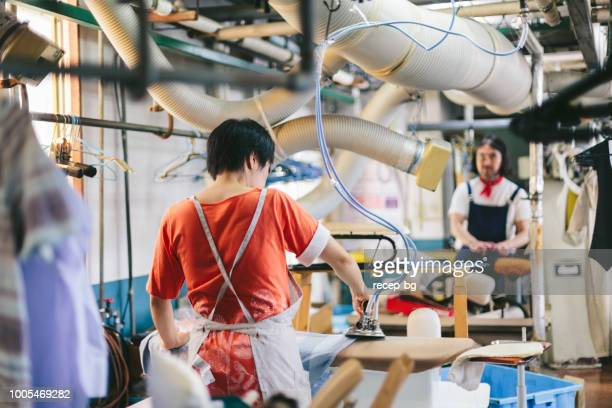 two people working in dry cleaning shop - dry cleaner stock pictures, royalty-free photos & images
