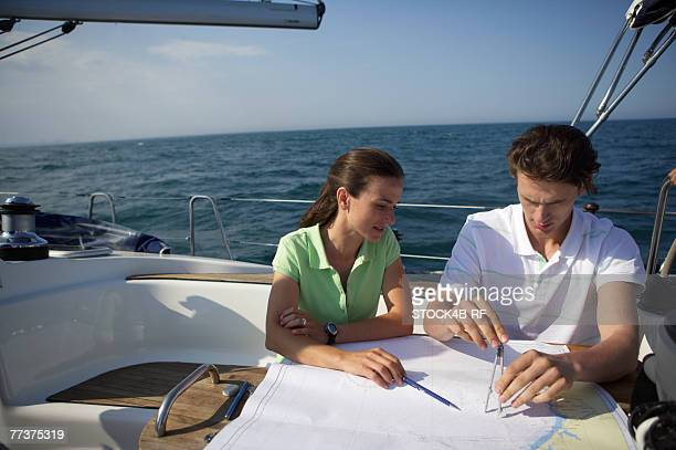 Two people working on a sea chart