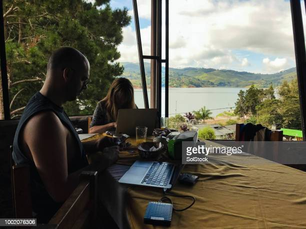 two people working on laptops at a table in a conference centre in the wilderness - cali colombia stock pictures, royalty-free photos & images