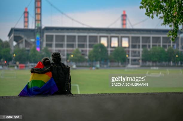 Two people wrapped in a Rainbow flag hug as they look at the Rheinenergie Stadium illuminated with the Rainbow colours, in Cologne, western Germany,...