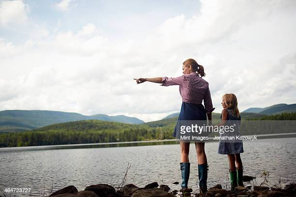 Two people,a woman and a child standing side by side and looking over water.