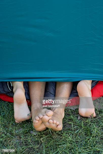 two people's feet sticking out of tent door. - playing footsie stock photos and pictures