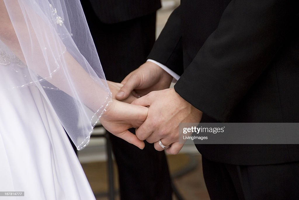 Two peoples hands joined at their wedding : Stock Photo