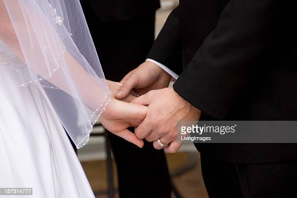 two peoples hands joined at their wedding - wedding vows stock pictures, royalty-free photos & images