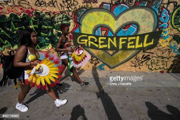 Two performers walk past a piece of graffiti relating to the Grenfell tower tragedy during the Notting Hill Carnival parade on August 28 2017 in...
