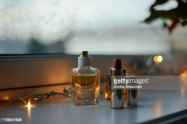 two perfume bottles and a red lipstick in a windowsill by a frozen window - kristina strasunske stock pictures, royalty-free photos & images