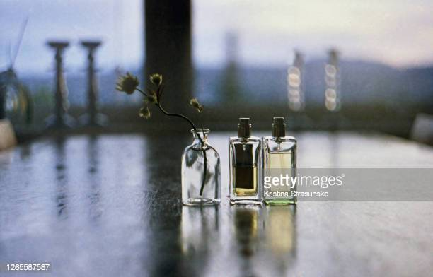 two perfume bottles and a vase with wildflower on a dining table - kristina strasunske stock pictures, royalty-free photos & images
