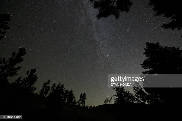 TOPSHOT Two Perseid meteors are seen near the Andromeda Galaxy and the Milky Way over Rocky Mountain National Park in Colorado in the early morning...