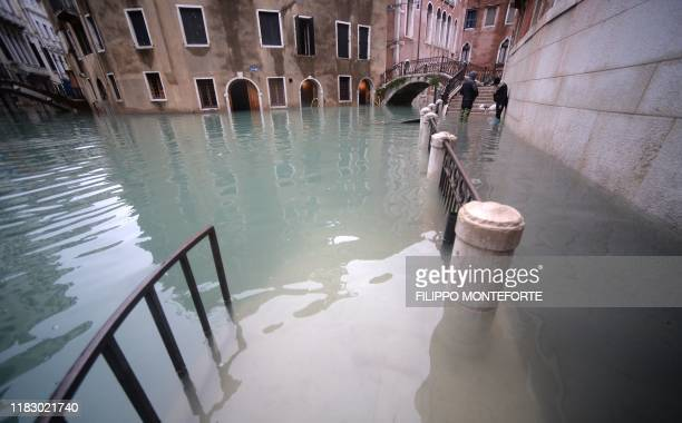 Two person stands in flooded street in Venice during acqua alta or high water of 160 centimetres on November 17 2019 Venice was braced on November 17...