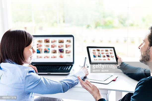 Two person team choosing images together on laptop and tablet