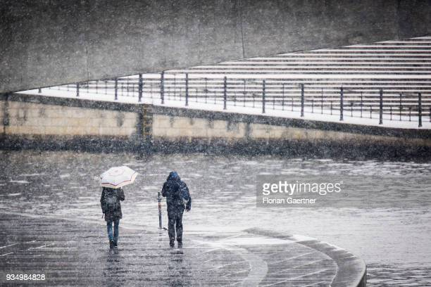 Two person walk during snow fall along the river Spree on March 20, 2018 in Berlin, Germany.