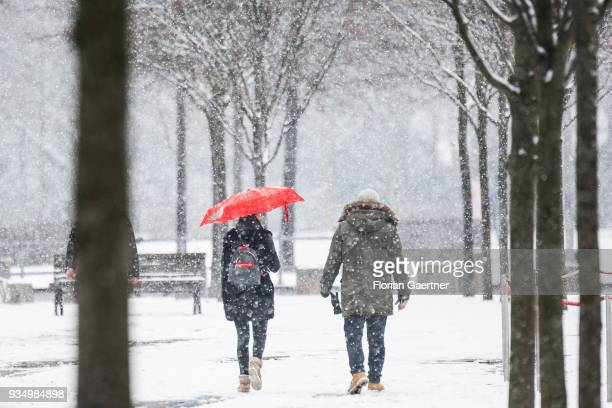 Two person walk during snow fall on March 20, 2018 in Berlin, Germany.