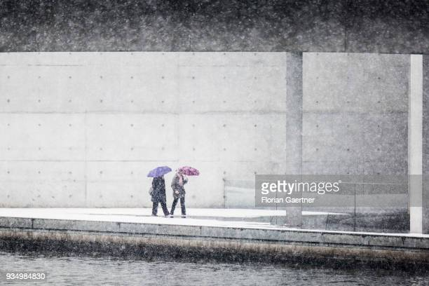 Two person with umbrellas walk during snow fall along the river Spree on March 20, 2018 in Berlin, Germany.