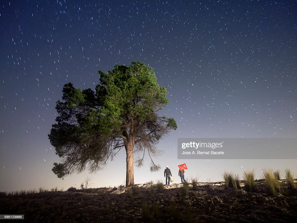 Two persons camiando with suitcases in the night : Stock Photo