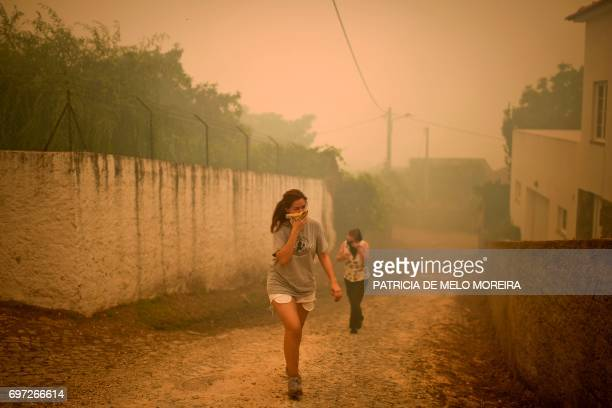 TOPSHOT Two persons cover their mouths and noses with a tissue during a wildfire threatening the village of Torgal Castanheira de Pera on June 18...
