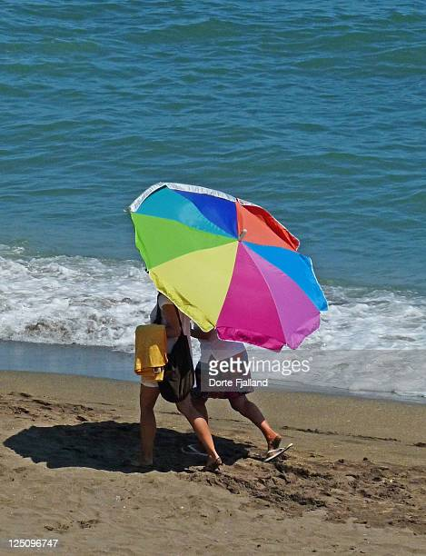 Two persons covered by parasol on beach