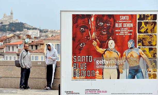 Two persons discuss near a poster showing Mexican wrestlers displayed in the front of the SaintCharles railway station in Marseille as part of the...